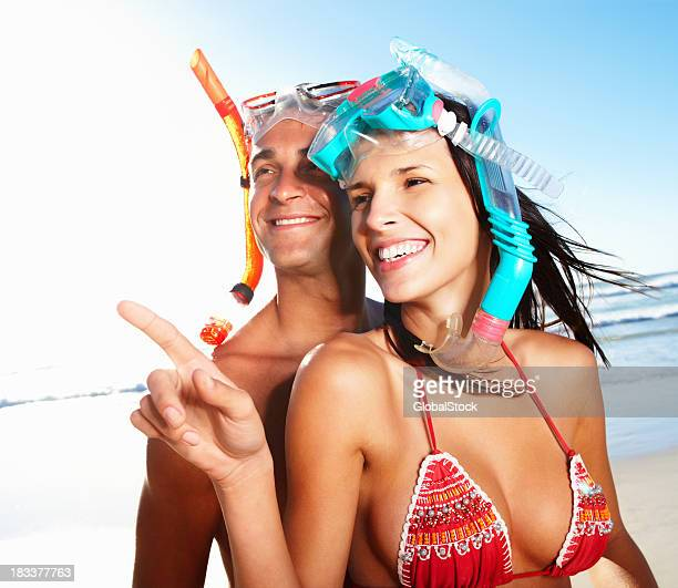 Woman pointing and smiling while wearing snorkel gear