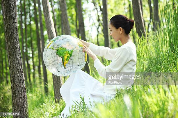woman pointing at globe ball in nature