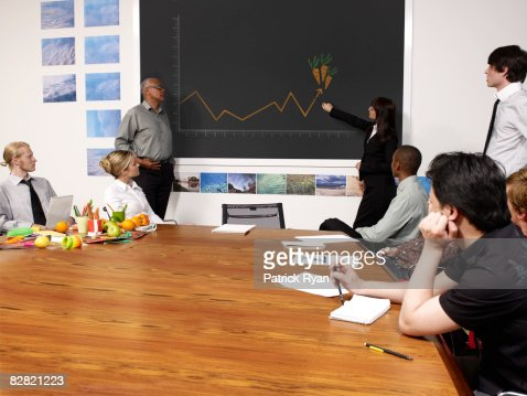 woman pointing at growth chart of carrots : Stock Photo