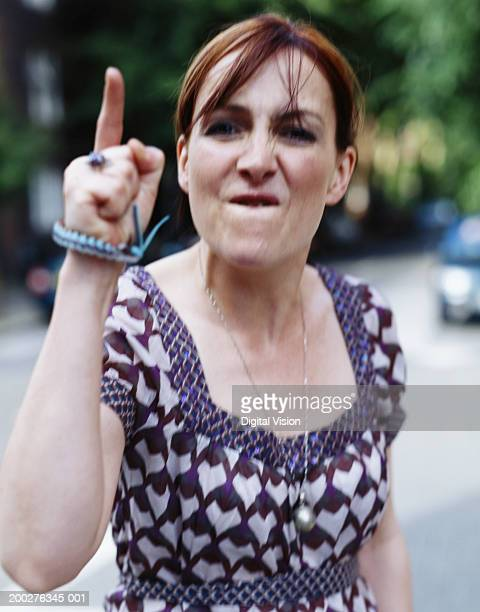 Woman pointing finger aggressively, portrait