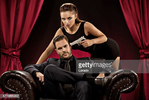 woman pointing gun to man sitting on chair