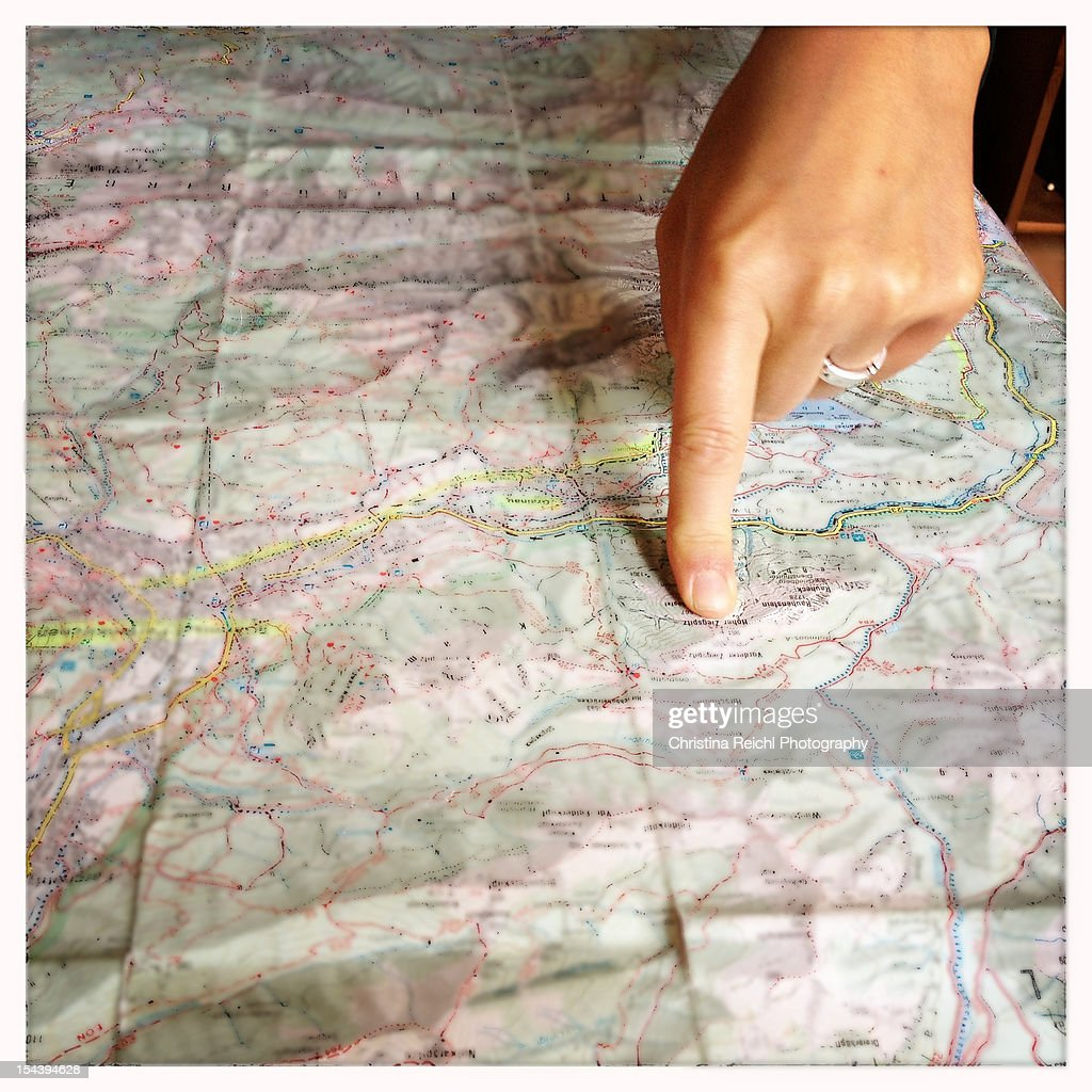 Woman pointing on a map with her index finger