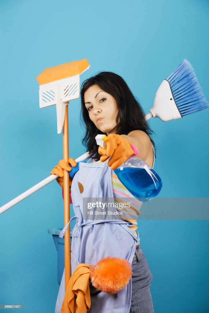 Woman pointing spray cleaner at camera : Stock Photo