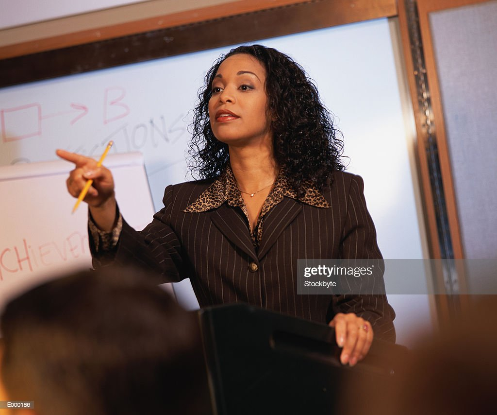 Woman pointing, standing in front of whiteboard : Stock Photo