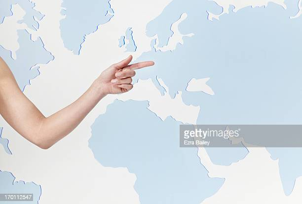 A woman pointing to a perspex world map.