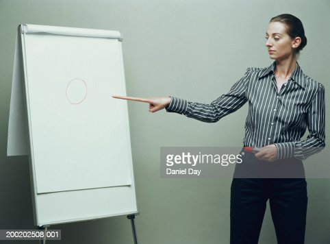 Woman pointing with long finger at flip chart (Digital Enhancement) : Stock Photo