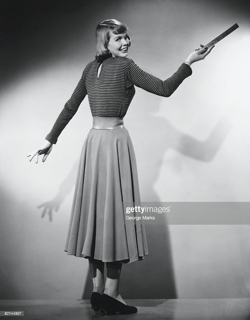Woman pointing with ruler in studio, (B&W) : Stock Photo