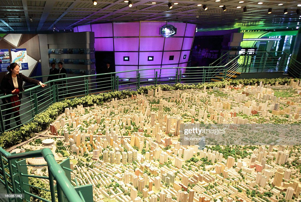 A woman points at a model of the city of Shanghai at the Shanghai Urban Planning Exhibition Center in Shanghai, China, on Tuesday, Jan. 29, 2013. China's economic growth accelerated for the first time in two years as government efforts to revive demand drove a rebound in industrial output, retail sales and the housing market. Photographer: Tomohiro Ohsumi/Bloomberg via Getty Images