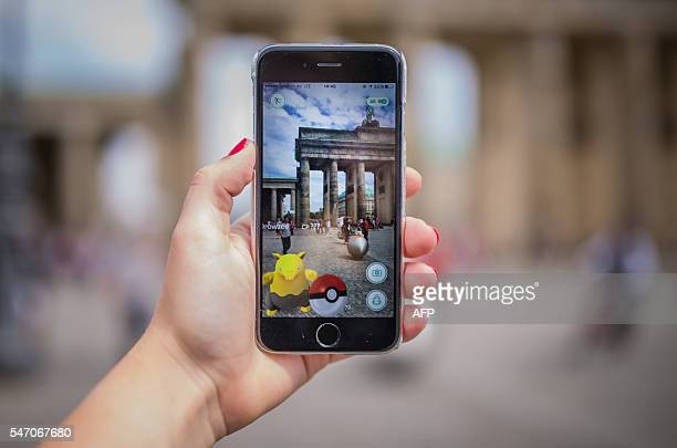 A woman points her smart phone at the Brandenburg Gate as she plays the Pokemon Go mobile game in Berlin on July 13 2016 The Pokemon Go mobile gaming...