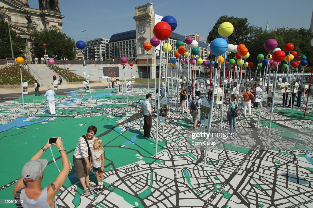 A woman points to the spot on a giant map of Berlin where she lives while her husband photographs her with her daughter on August 29, 2012 in Berlin, Germany. The map, which is in 1:775 scale and includes giant, coloured pins to mark sites of historical significance, is part of ongoing exhibitions and events ahead of Berlin's 775th anniversary, which the city will mark with a celebration scheduled for the end of October.