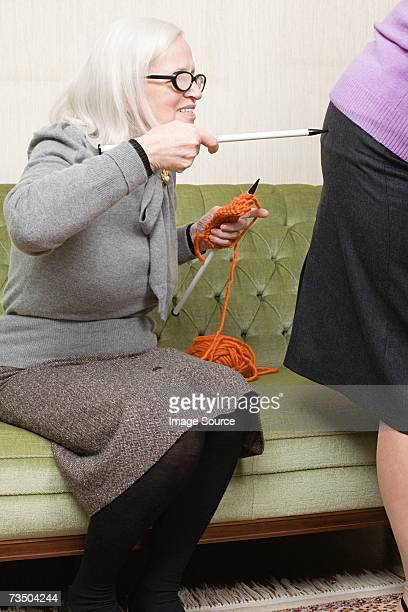 Woman poking friend with a knitting needle