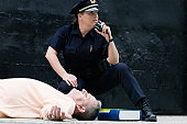 Police officer in front of an unconscious man communicating on a CB radio for help