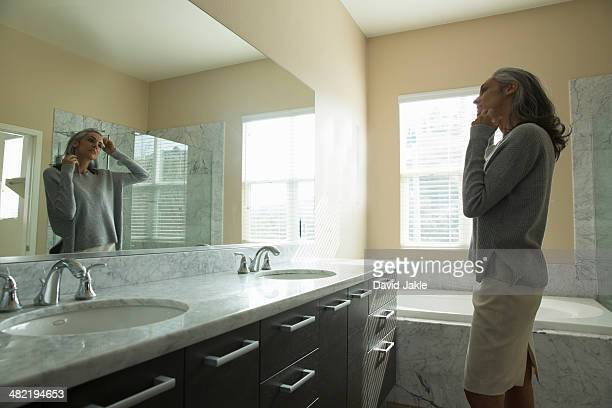 Woman pondering in front of mirror