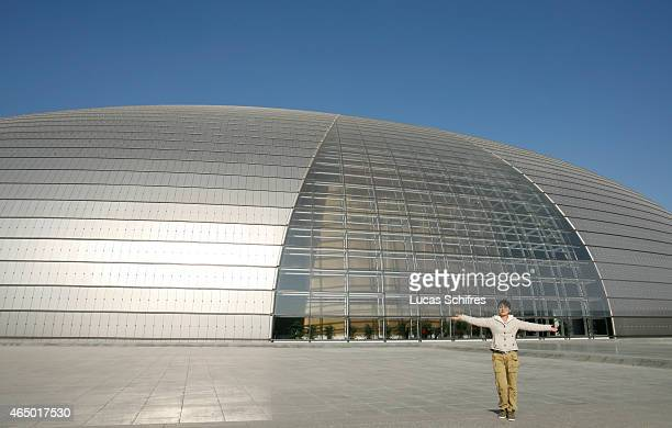 A woman posed for a photograph by Beijing National Grand Theatre on November 20 2008 in Beijing China The National Centre for the Performing Arts was...