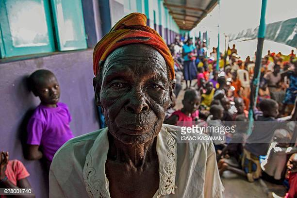 TOPSHOT A woman poses as she arrives to watch on tv the screening of the start of the ICC trial of former child soldierturnedwarlord Dominic Ongwen...