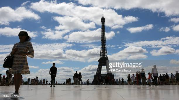 A woman poses at the Trocadero esplanade in front of the Eiffel tower on June 25 in Paris / AFP PHOTO / LUDOVIC MARIN