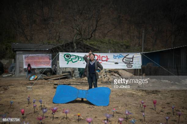 A woman poses for a photo before a banner as residents of Seongju county participate in a protest outside a golf course being used as the site for...