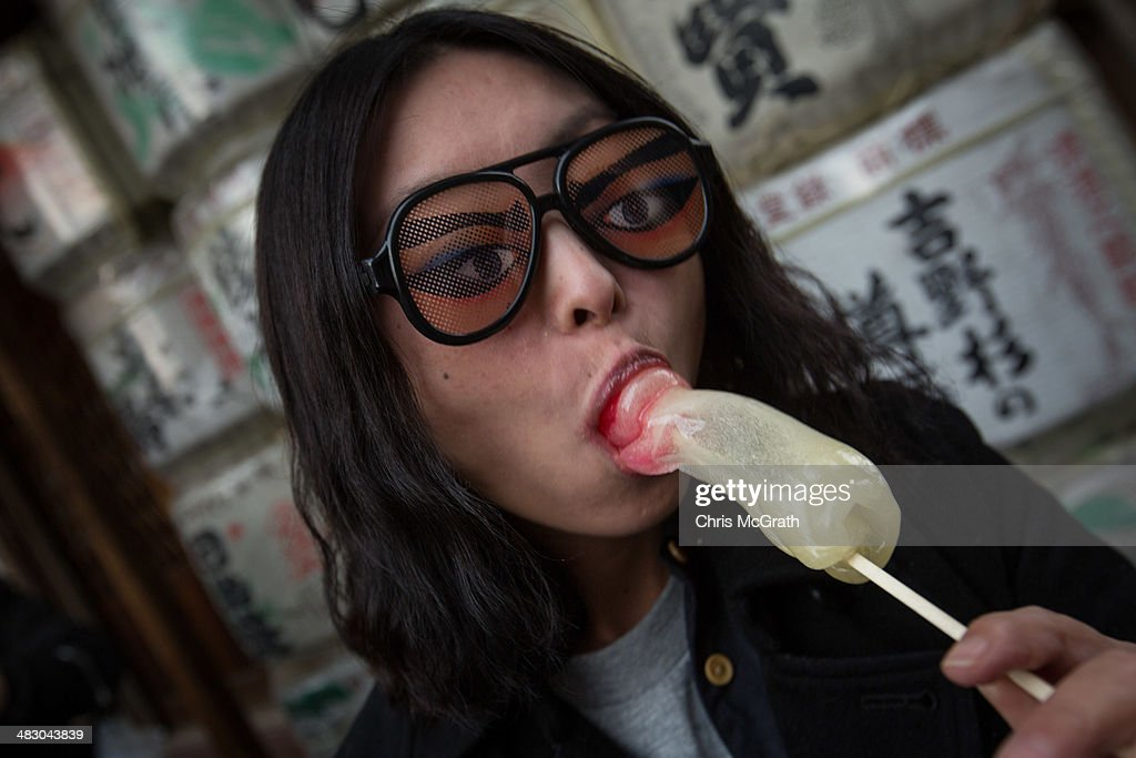 A woman poses for a photo eating a phallicshaped candy lollipop during Kanamara Matsuri on April 6 2014 in Kawasaki Japan The Kanamara Festival is...