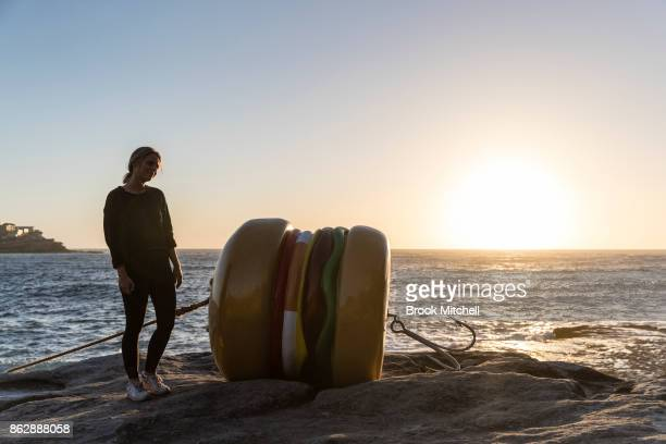 A woman poses for a photo next to the work 'That's a Tasty Burger' by James Dive at Sculpture By The Sea at Bondi Beach on October 19 2017 in Sydney...