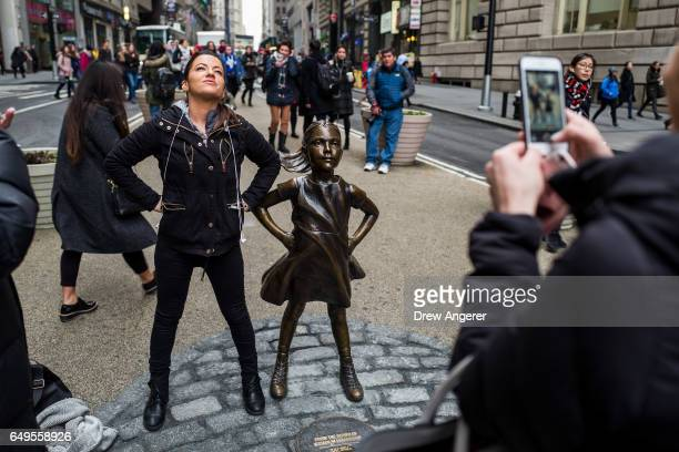 A woman poses for a photo with 'The Fearless Girl' statue across from the iconic Wall Street charging bull statue March 8 2017 in New York City State...