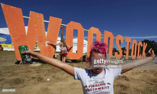 A woman poses for a photograoher during the socalled 'Woodstock Stop' openair festival in the Polish town of Kuestrin on August 1 2009 400000 people...