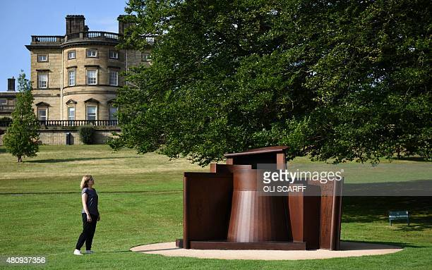 A woman poses for a photograph alongside a sculpture entitled 'Dream City' by artist Sir Anthony Caro as it stands on display as part of the...