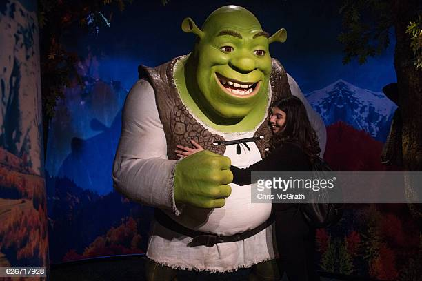 A woman poses for a photograph as she hugs a waxwork figure of animated movie character Shrek on display at Turkey's first Madame Tussauds Wax Museum...