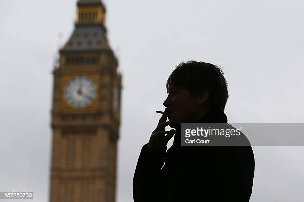 A woman poses for a photograph as she smokes a cigarette on October 15 in Parliament Square in London England Following a report called 'Better...