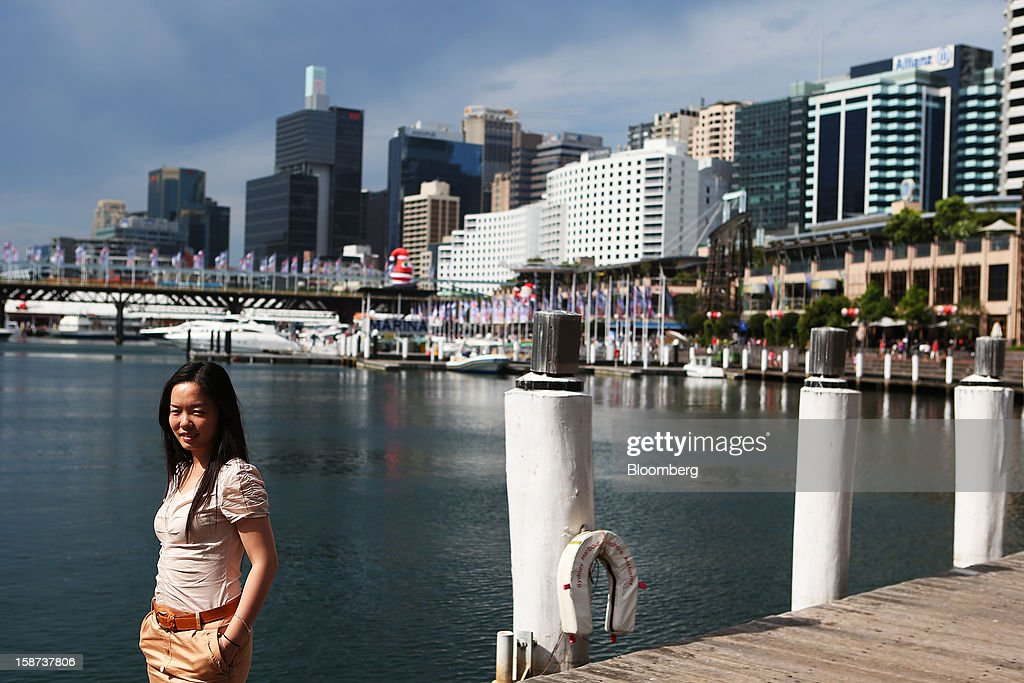 A woman poses for a photograph by the water in the Darling Harbour precinct in Sydney, Australia, on Monday, Dec. 24, 2012. At least 150,000 people from mainland China and across Asia are projected to descend on Sydney, Australia's most populous city, during the New Year's Eve and Chinese New Year period. Photographer: Brendon Thorne/Bloomberg via Getty Images