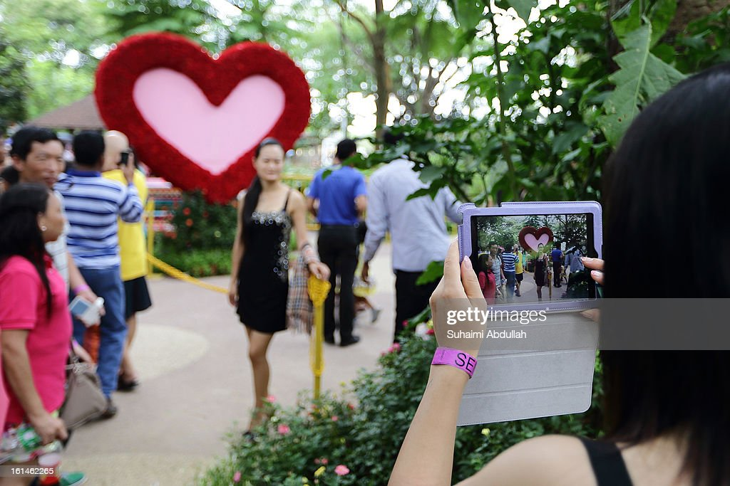 A woman poses for a photograph in front of a heart shaped floral display at the Sentosa Flowers exhibition at Palawan Beach on February 11, 2013 in Singapore. Millions of spring flowers decorate the island in celebration of the Chinese New Year, the year of the Snake.