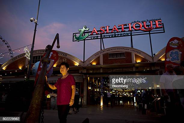 A woman poses for a photograph in front of an illuminated sign for Asiatique The Riverfront openair mall displayed at the market in Bangkok Thailand...
