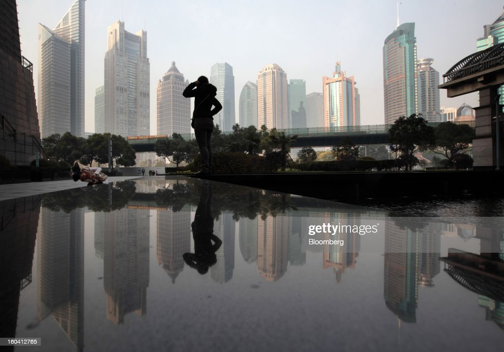 A woman poses for a photograph in front of commercial buildings in the Pudong area of Shanghai, China, on Wednesday, Jan. 30, 2013. China's economic growth accelerated for the first time in two years as government efforts to revive demand drove a rebound in industrial output, retail sales and the housing market. Photographer: Tomohiro Ohsumi/Bloomberg via Getty Images