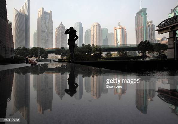 A woman poses for a photograph in front of commercial buildings in the Pudong area of Shanghai China on Wednesday Jan 30 2013 China's economic growth...