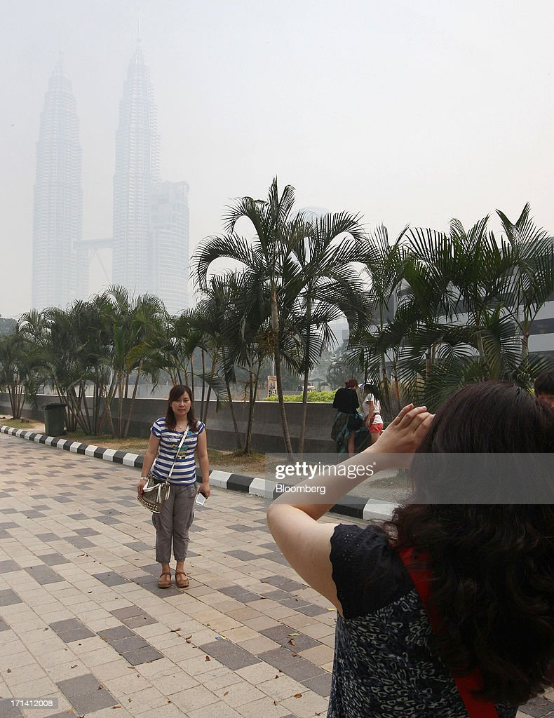A woman poses for a photograph in front of the Petronas Towers as they are shrouded in smog in Kuala Lumpur, Malaysia, on Monday, June 24, 2013. Malaysia called for a meeting of Southeast Asian ministers as early as next week after haze from illegal Indonesian forest fires reached hazardous levels in parts of the region. Photographer: Goh Seng Chong/Bloomberg via Getty Images