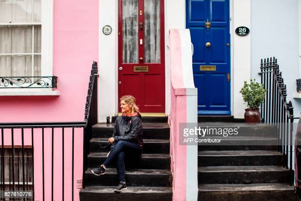 A woman poses for a photograph pn the steps of a brightly painted house on Denbigh Terrace near Portobello Road Market in the Notting Hill district...