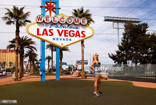 A woman poses for a photograph under the 'Welcome to Las Vegas' sign in Las Vegas Nevada US on Thursday March 20 2014 The average gambling budget of...