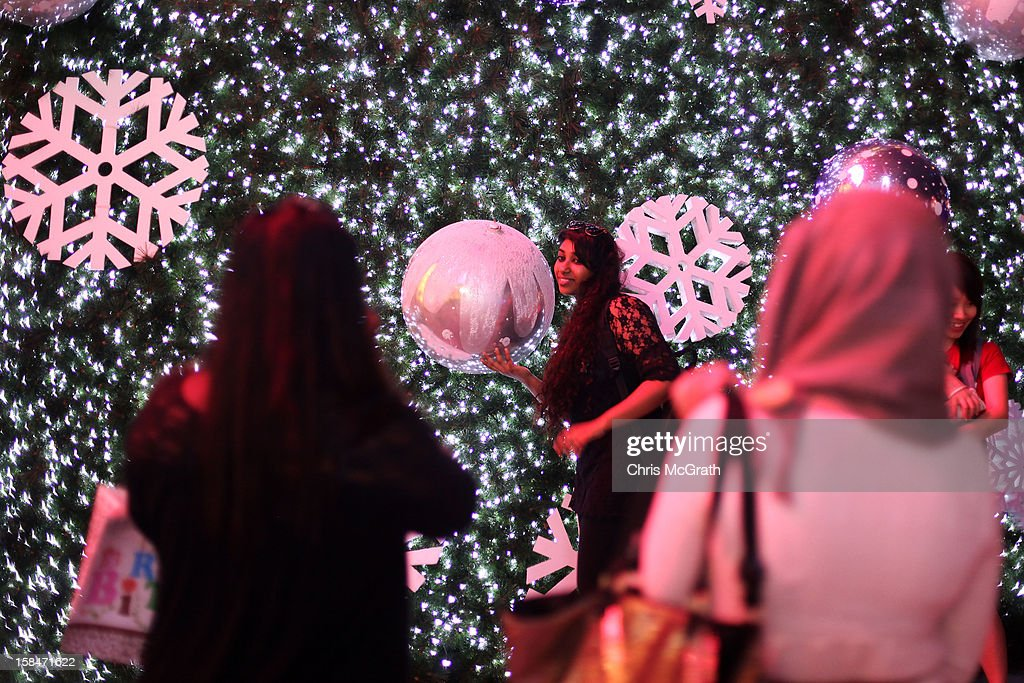 A woman poses for a photograph with a large decorated Christmas tree on display at Orchard road on December 17, 2012 in Singapore.