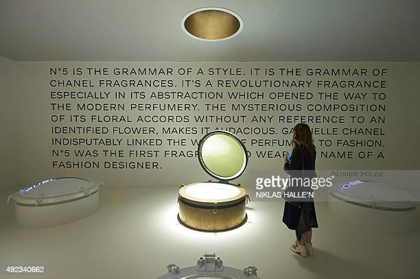 A woman poses for a photograph with an installation dedicated to the Chanel No 5 perfume during a pressview of 'Mademoiselle Privé' a joint...