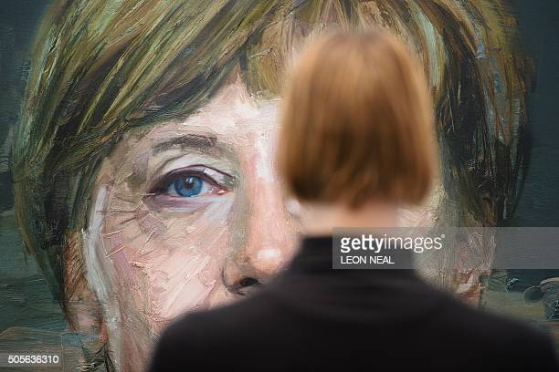 TOPSHOT A woman poses for a photograph with artwork entitled 'Portrait of Angela Merkel' by Colin Davidson during a press preview at the London Art...