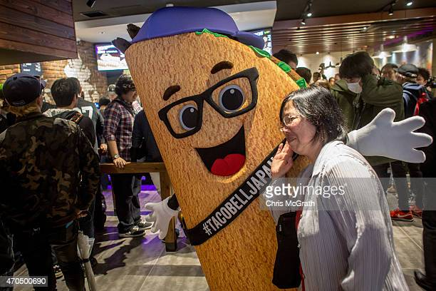 A woman poses for a photograph with the Tac bell mascot inside the new Taco Bell store during the official opening on April 21 2015 in Tokyo Japan...