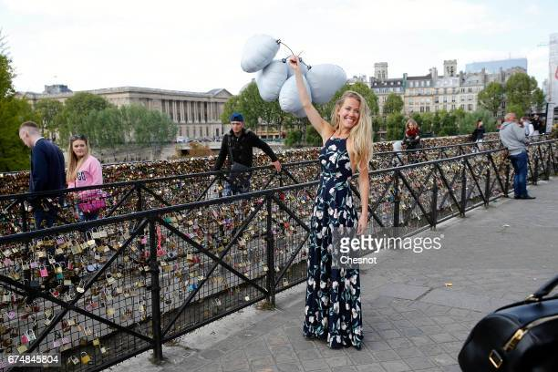 A woman poses for a photographer in front of love padlocks on the Pont Neuf on April 29 2017 in Paris France The Paris City Hall will organize on May...