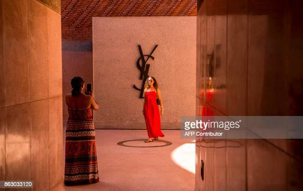 A woman poses for a picture at the entrance of the new Yves Saint Laurent museum in the Moroccan city of Marrakesh on October 19 2017 A fusion of the...