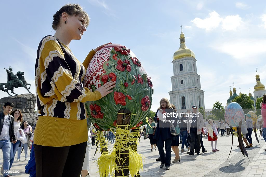 A woman poses for a picture by a Pysanka, a traditional Easter egg, decorated by Ukrainian artists to celebrate Orthodox Easter and spring time, during Ukrainian Pysanka Festival in Kiev on May 1, 2016. 374 big eggs and 40,000 smaller one are presented at St. Sophiya Square in Kiev for the occasion. / AFP / Sergei SUPINSKY