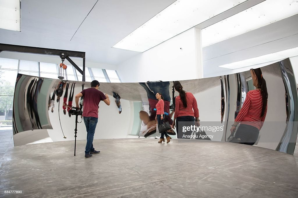 A woman poses for a picture in front of 'C-Curve' by Indian-British sculptor Anish Kapoor during the exhibition press preview of 'Archaeology: Biology' at University Museum of Contemporary Art in Mexico City, Mexico on May 27, 2016. This exhibition offers a wide-ranging perspective on Kapoors workwith sculptures dating from 1980 to 2016.