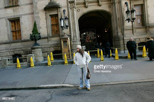 A woman poses for a picture outside the main entrance to the Dakota the former home of slain pop star and activist John Lennon December 8 2005 in New...