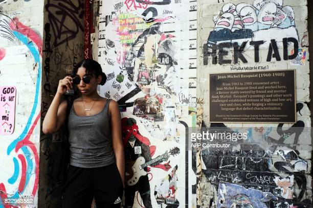 A woman poses for photo next to a plaque honoring artist JeanMichel Basquiat outside the studio where he used to work in New York on July 10 2017...