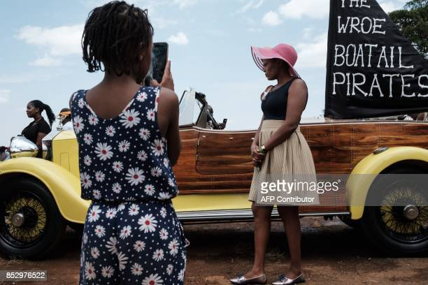 A woman poses for photographs in front of a 1934 vintage Rolls Royce Phantom II owned and restored by Kenyan classic and vintage car enthusiast John...
