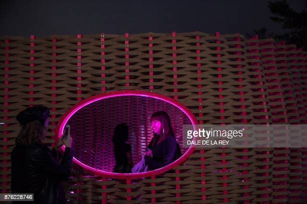 A woman poses for photographs inside an installation at the Clockenflap music festival in Hong Kong on November 19 2017 / AFP PHOTO / DALE DE LA REY