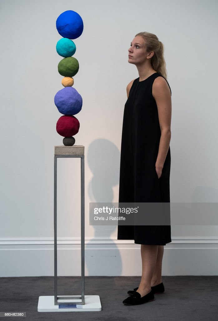 A woman poses for photographs next to Stack 7, Ultramarine Blue by Annie Morris, estimated at £5,000-£7,000, during an Art for Grenfell press call at Sotheby's Art for Grenfell preview on October 12, 2017 in London, United Kingdom. The 'Art for Grenfell' auction will take place on October 16 2017 and includes work by contemporary artists.