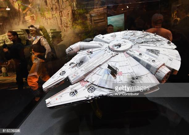 A woman poses for photos beside a Star Wars Millennium Falcon during the D23 expo fan convention at the Convention Center in Anaheim California on...